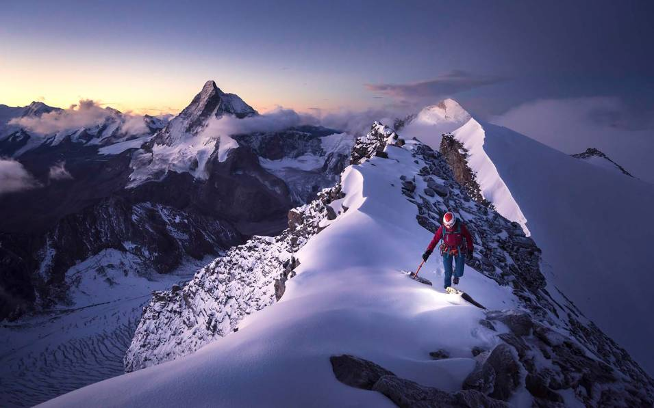 Person climbing the peak of a snowy mountain range