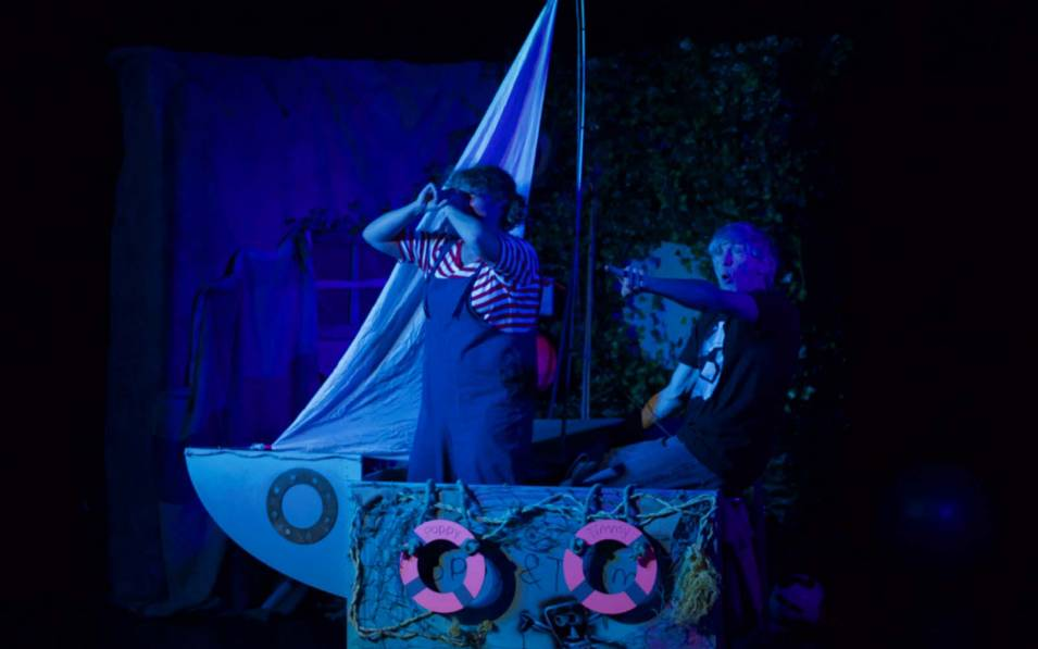 Production image of two actors on a boat in blue lighting