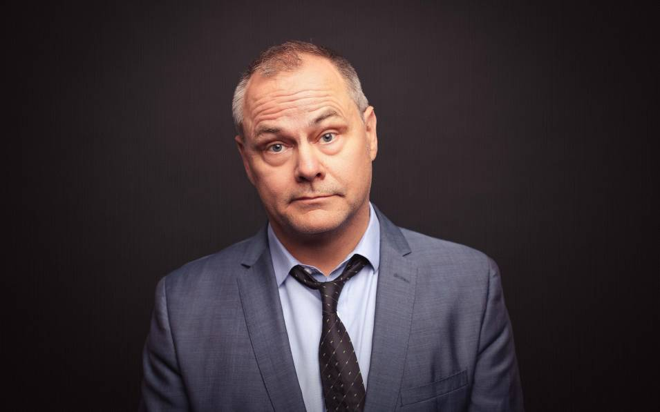 Jack Dee posing in grey suit and black tie