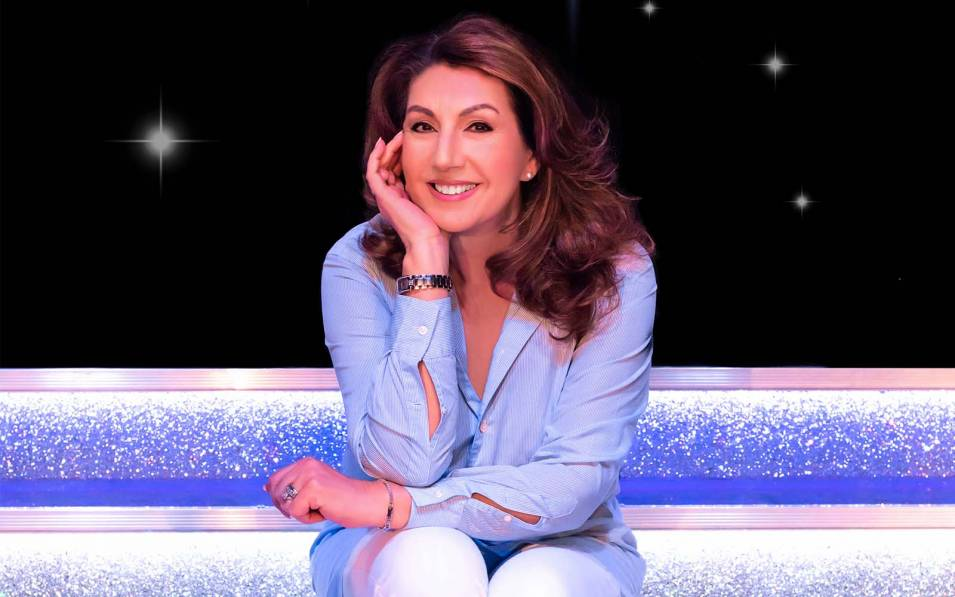 Jane McDonald sat down smiling with her arm on her knee and hand on her face