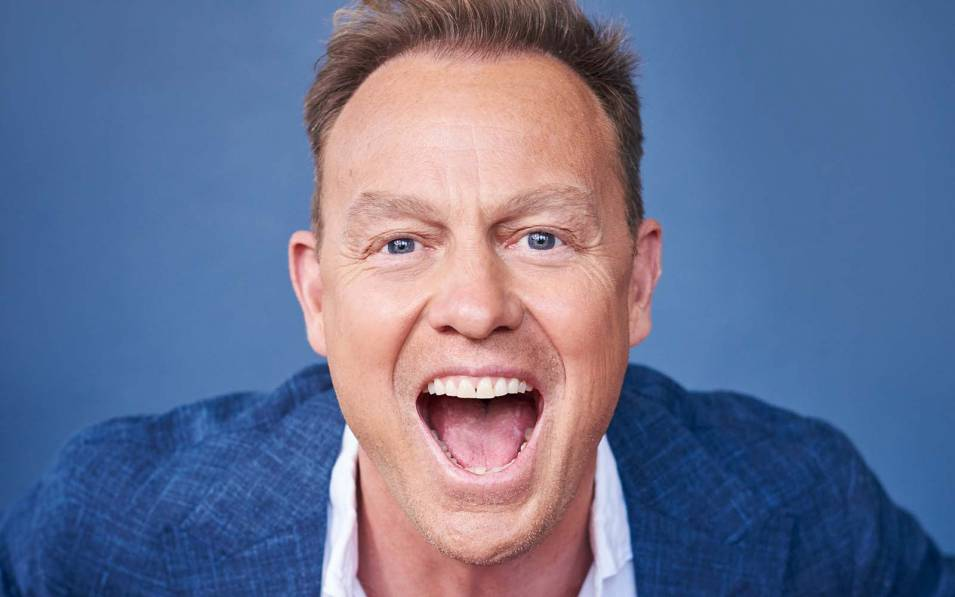 Jason Donovan smiling with his mouth wide open
