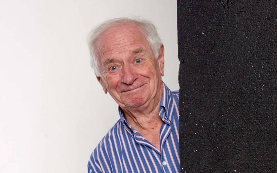 Johnny Ball smiling behind black concrete wall