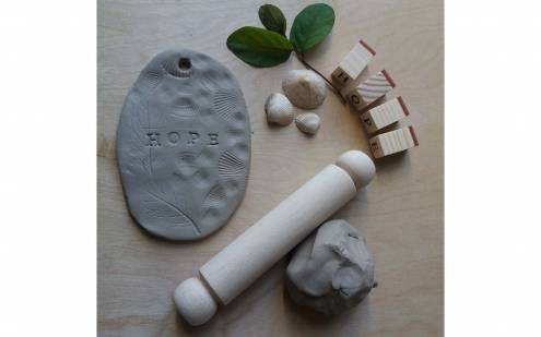 Photograph of clay, a rolling pin and some leaves