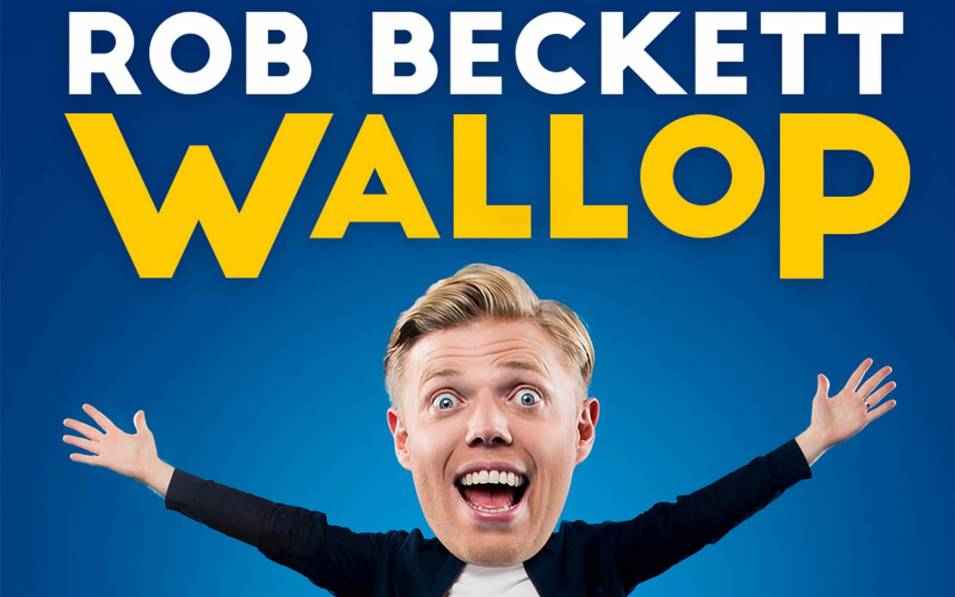 Rob Beckett smiling with his mouth open and hands in the air