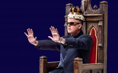 King sat on thrown with his hands pushing forward