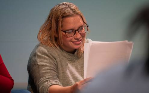 An actress smiling while reading her script