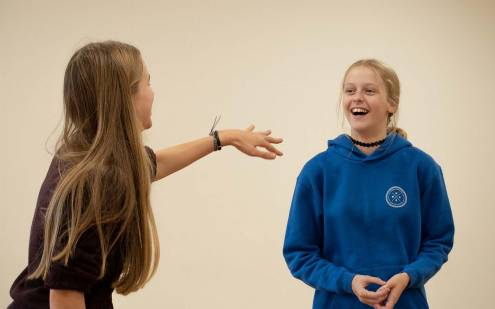 One girl pointing and another girl laughing