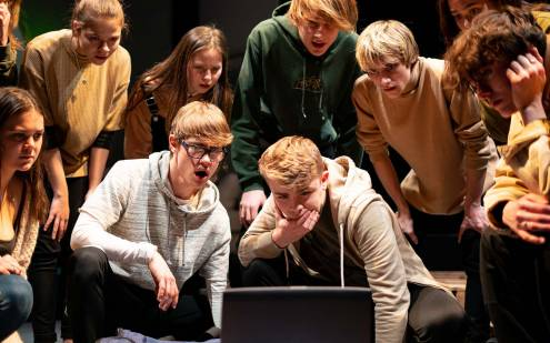 Actors gathered around a computer screen