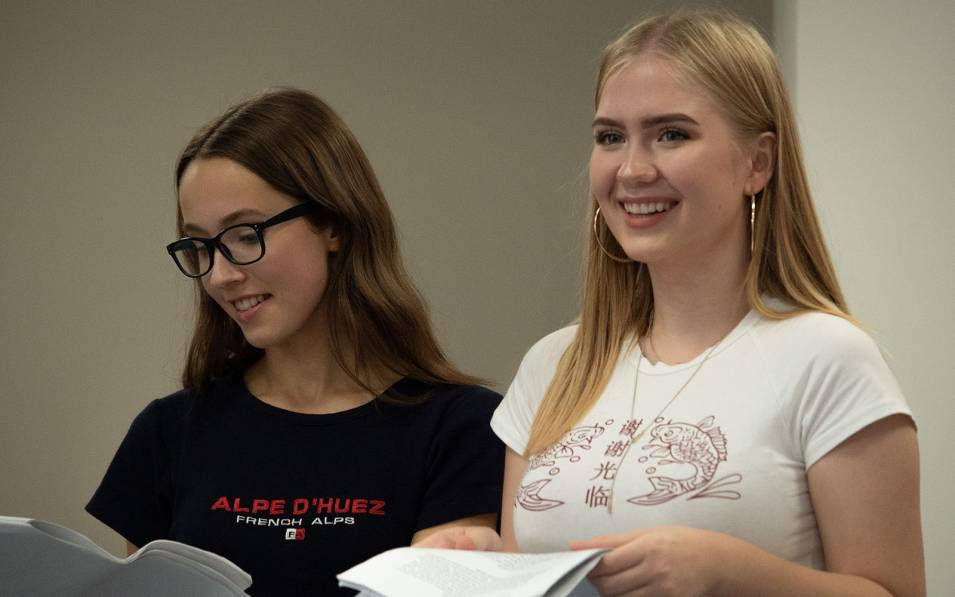 Two young writers smiling and looking at their scripts