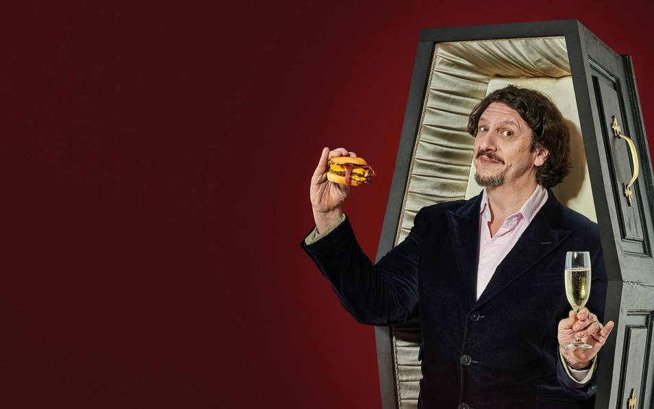 Jay Rayner posing inside a coffin, holding a burger and a glass of champagne