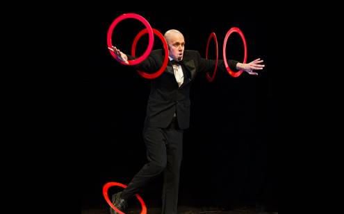 Circus performer spinning rings on his arms and legs