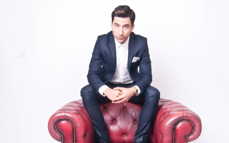 Russell Kane sitting on the top of a leather chair.