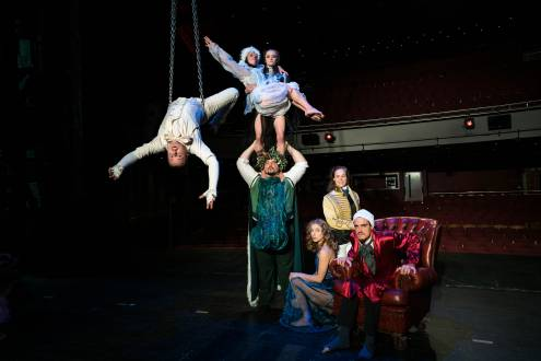 An acrobat hanging backwards off chains in the air. A strongman carrying two other performers on his shoulders and other members of Lost in Translation Circus around them