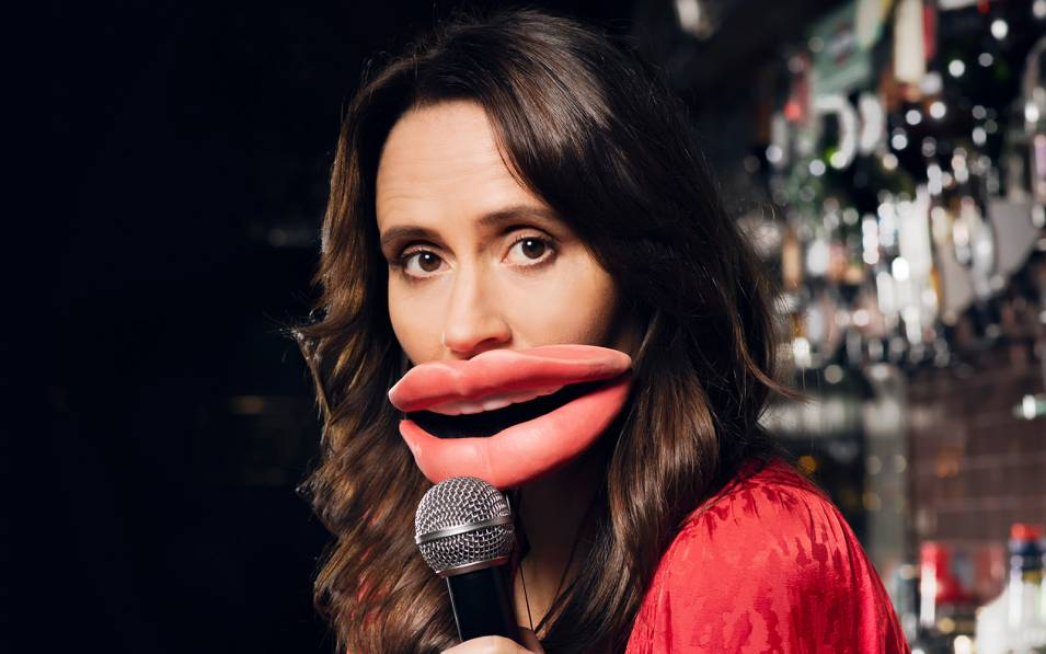 Nina Conti holding a microphone with large plastic lips covering her mouth