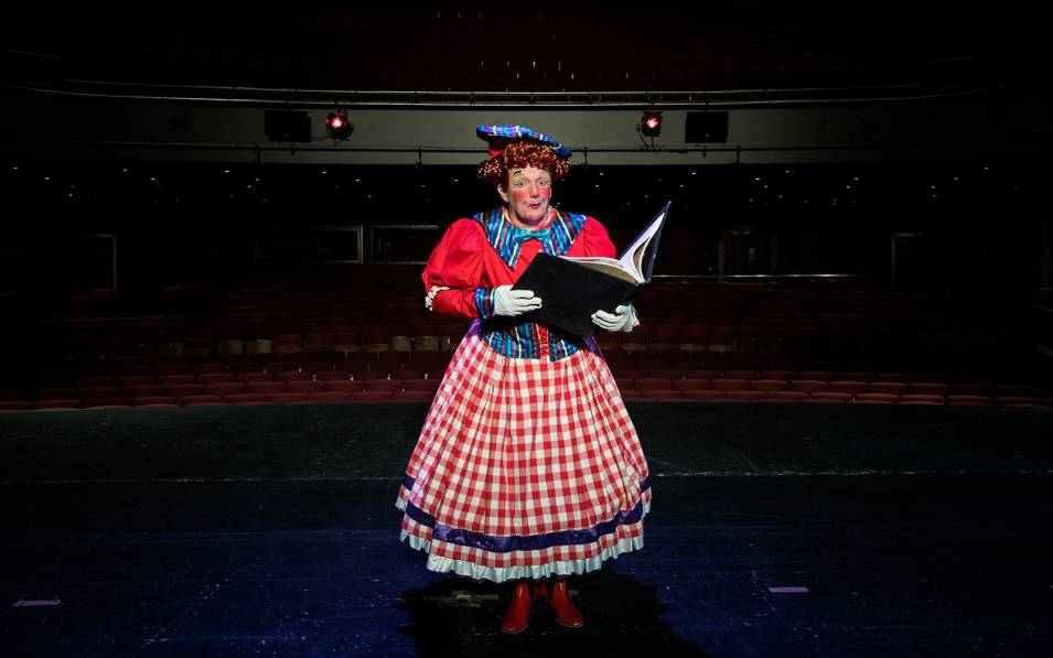 Richard Gauntlett dressed as a dame, holding a large storybook, on stage at the Theatre Royal