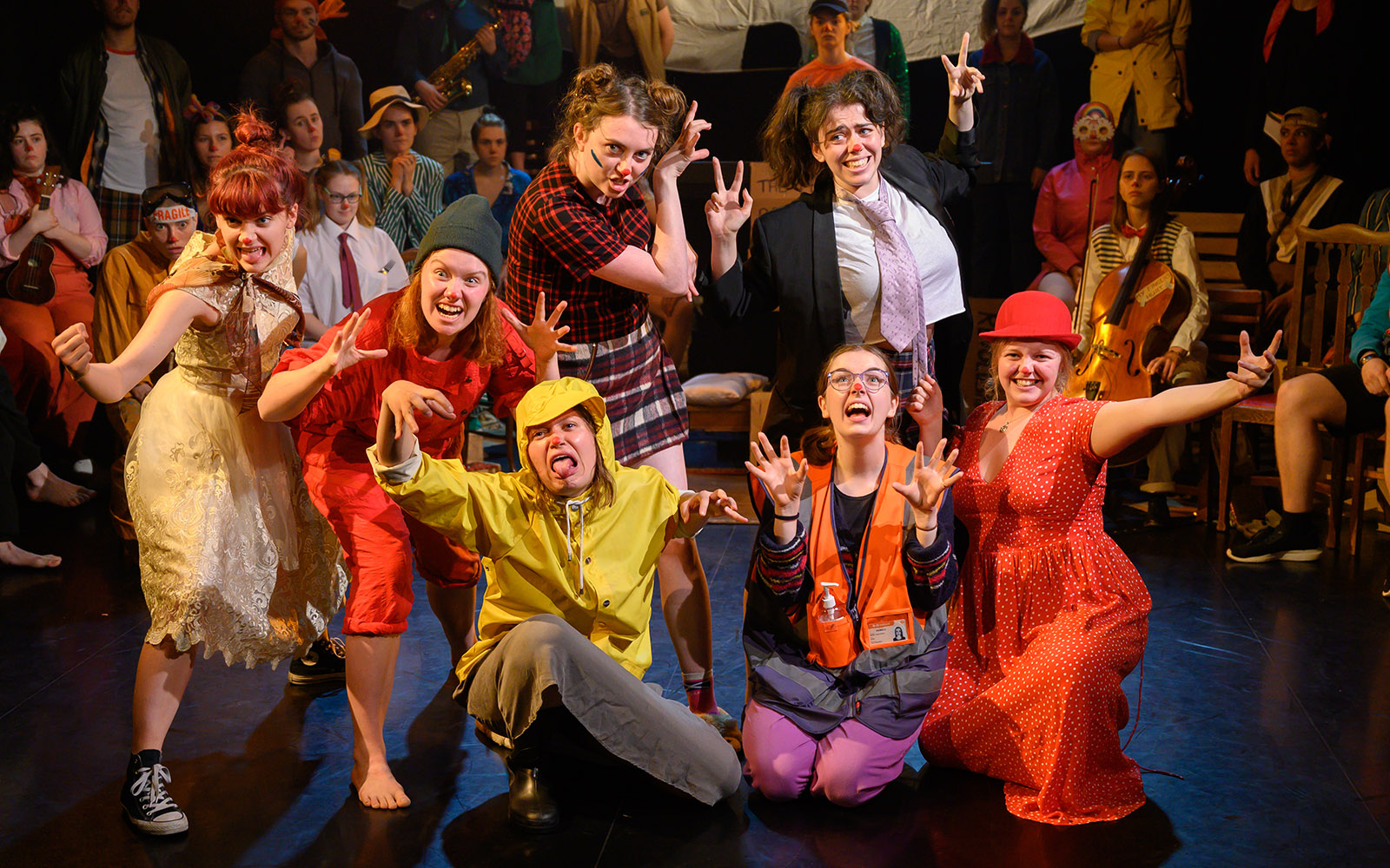 A colourful scene of drama students posing on stage.