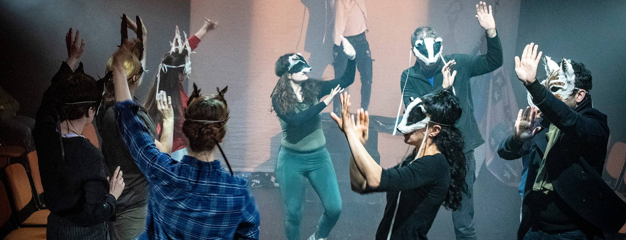 Actors dancing on stage wearing animal masks.