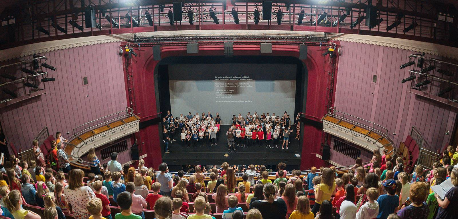A large group of children in the Norwich Theatre Royal auditorium